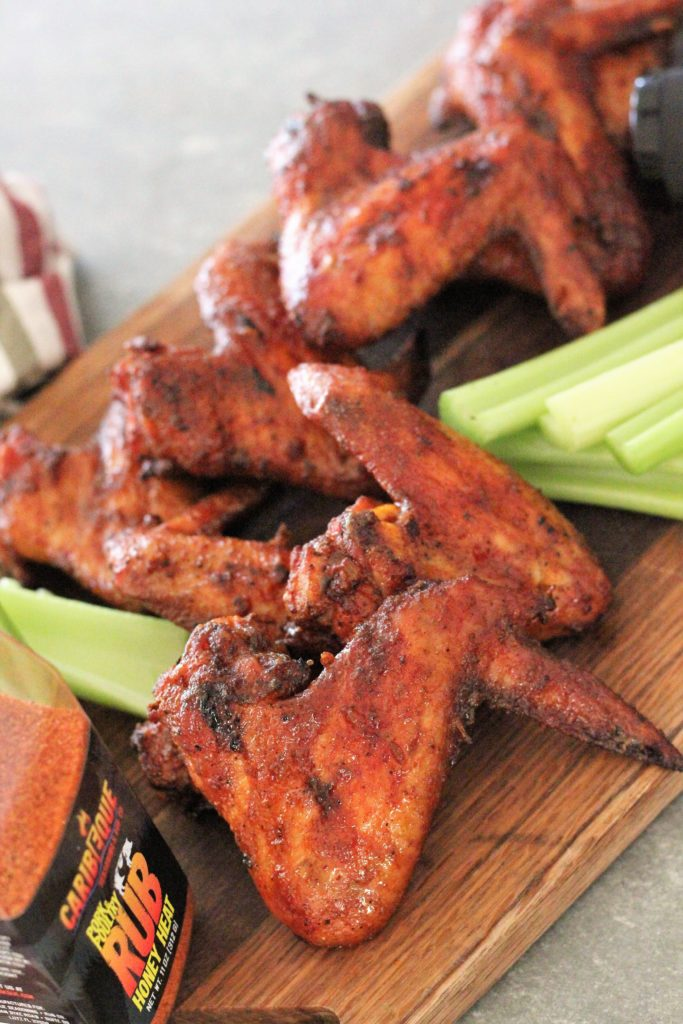 Honey Heat Smoked Chicken wings and celery arranged on a wood cutting board.