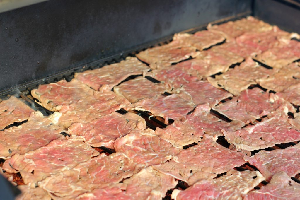 sliced beef laid flat in a smoker