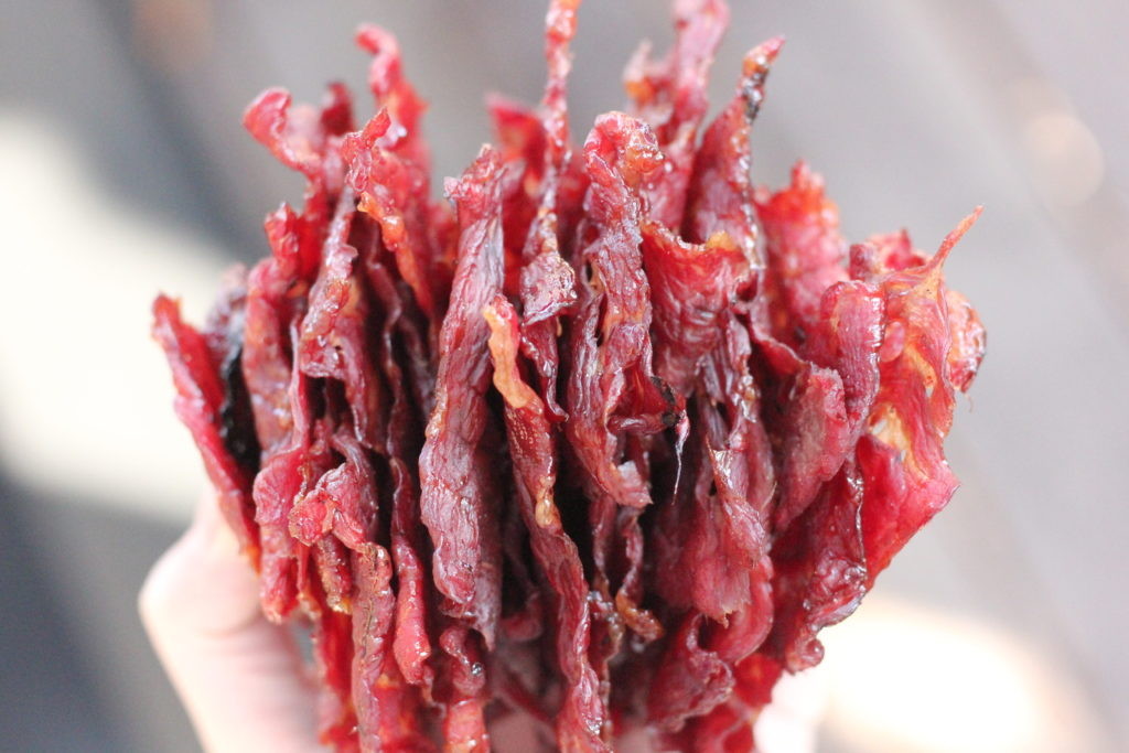A hand holding a stack of finished beef jerky