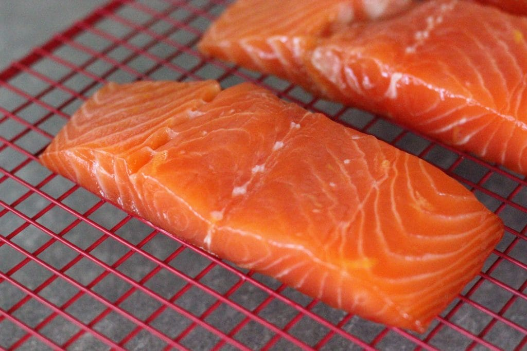 two pieces of salmon on a red cooling rack.