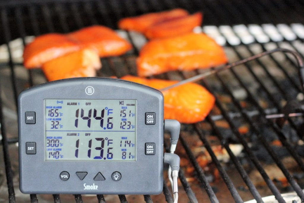 Smoked Salmon on the grill grate with a digital meat thermometer reading 144 degrees farenheit.
