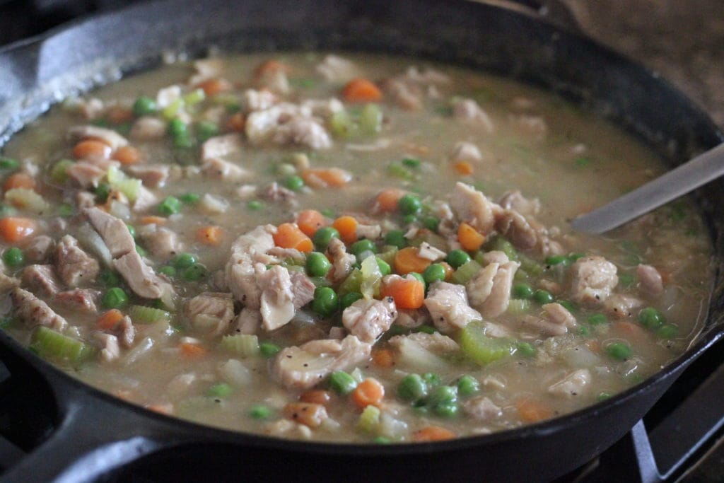 Cast iron skillet full of chopped chicken, vegetables, and chicken stock.