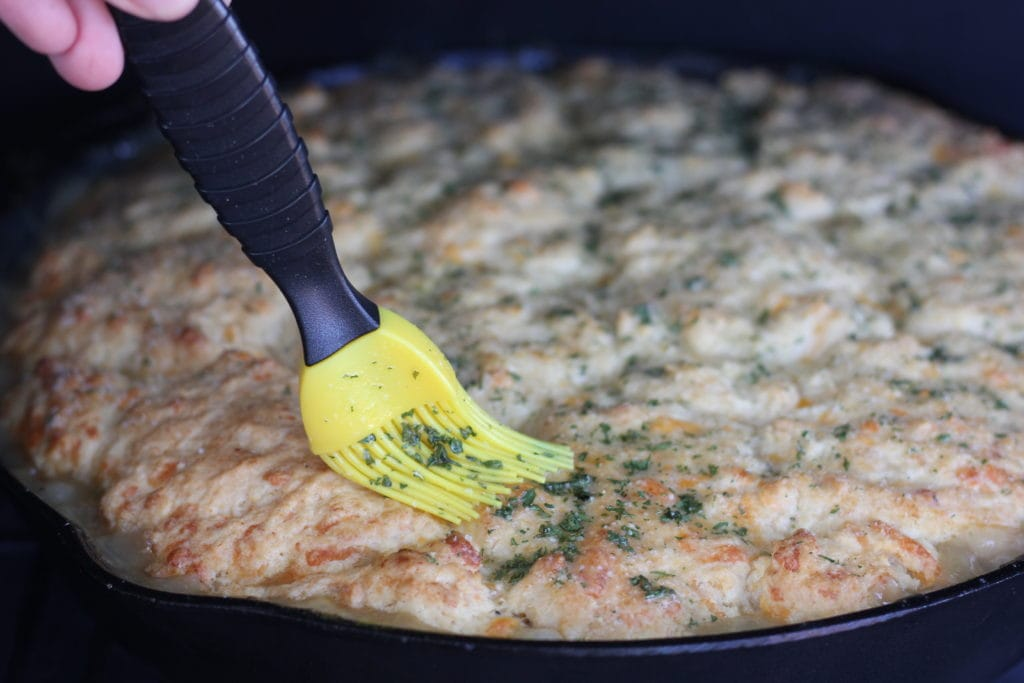 Yellow basting brush spreading garlic butter and parsley on top of the cheddar biscuit crust of a skillet pot pie.