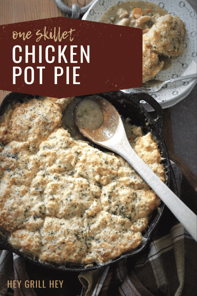 """Chicken pot pie with a cheddar biscuit crust in a cast iron skillet next to a bowl full of pot pie. Text overlay reads: """"One Skillet Chicken Pot Pie."""""""
