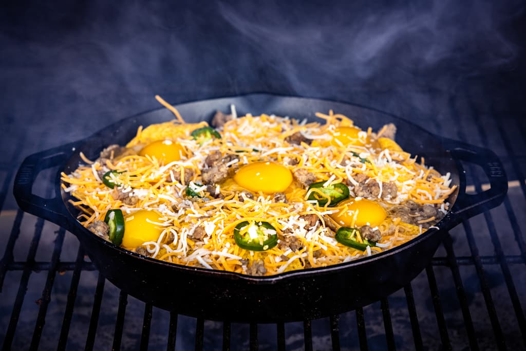Loaded breakfast nachos in a cast iron skillet on the grill grates of a smoker surrounded by blue smoke.