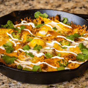 Loaded breakfast nachos in a cast iron skillet garnished with sour cream and fresh cilantro.