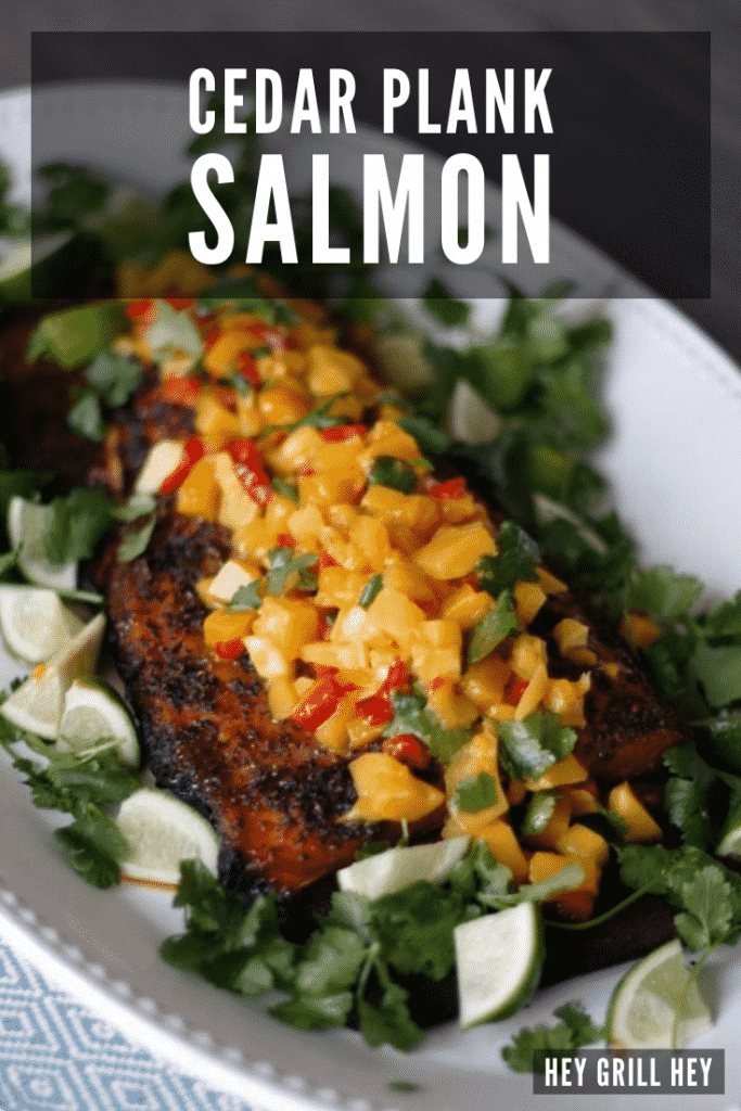 Cedar plank grilled salmon topped with mango salsa on a white oval plate.