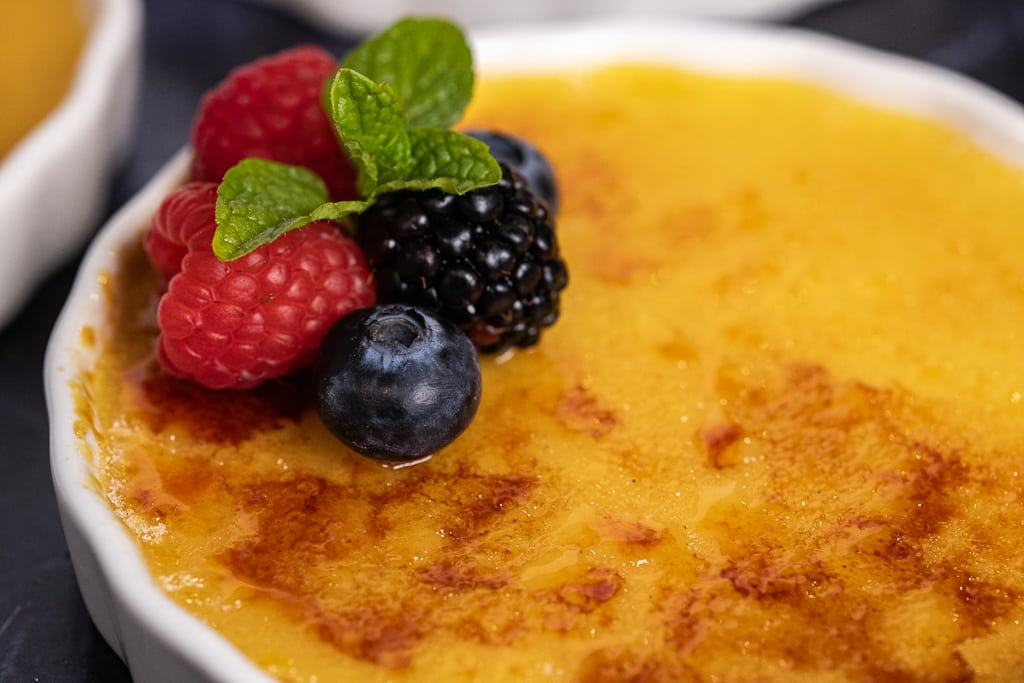 One ramekin of caramel creme brulee topped with fresh berries and a mint leaf.