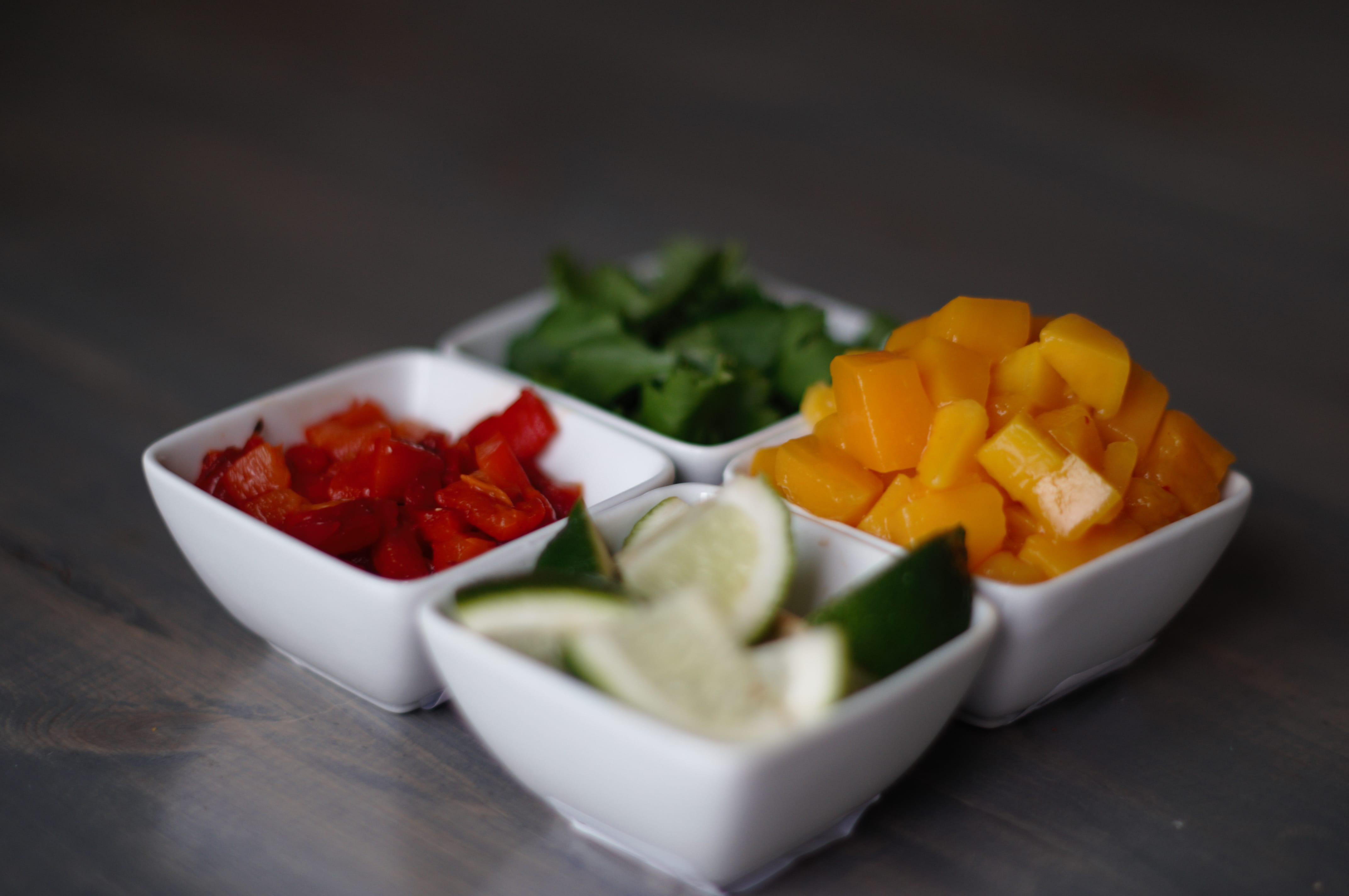 veggies in bowls on wooden table.