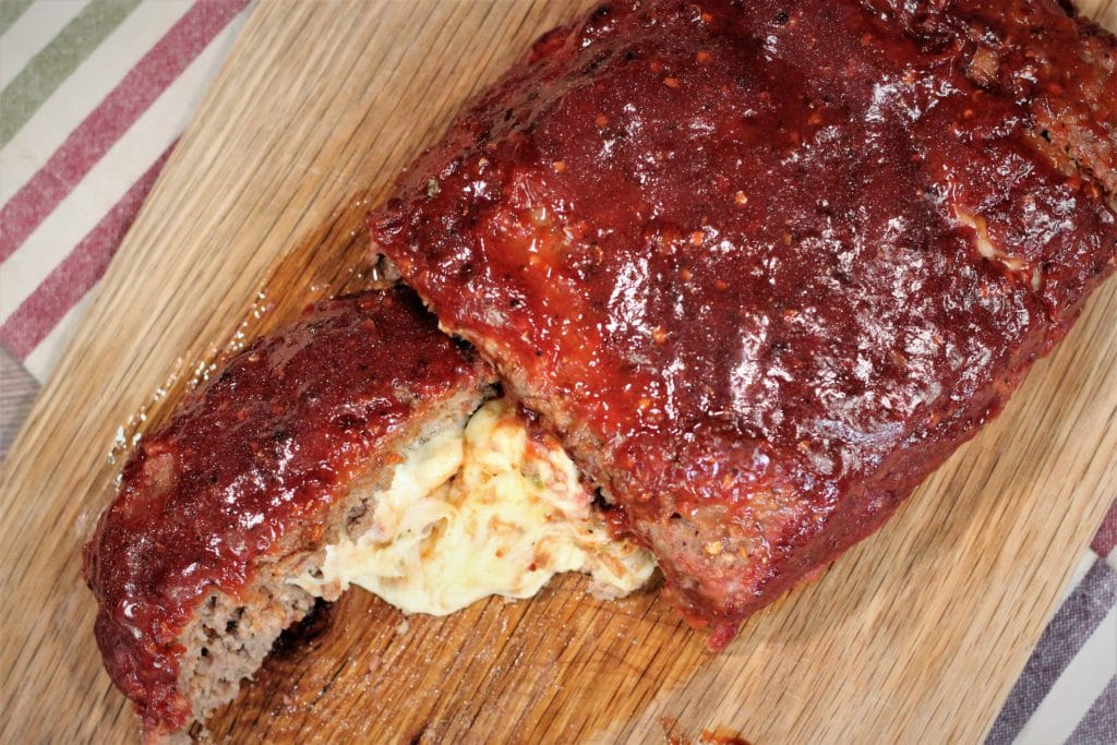Glazed meatloaf on a wood cutting board with a single slice cut and melted cheese between