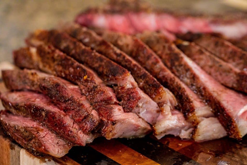 Sliced Tomahawk Steak served on a wooden cutting board.