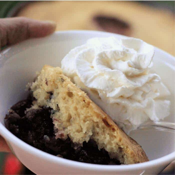 Cherry berry dutch oven cobbler and whipped cream in a white bowl.