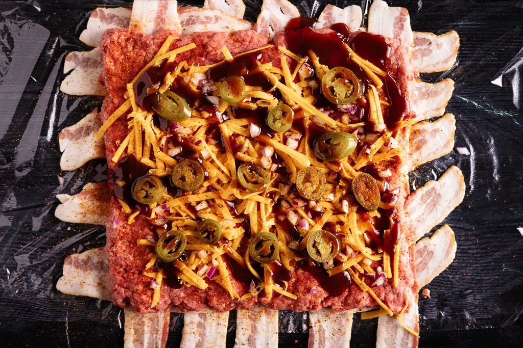 Bacon weave with ground beef, cheddar cheese, sliced jalapenos, and BBQ sauce on top.