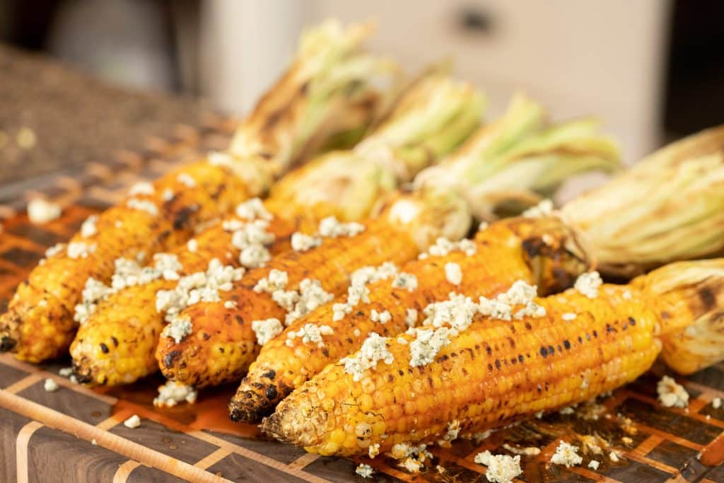 5 ears of grilled corn on a wooden cutting board with blue cheese crumbled on top.