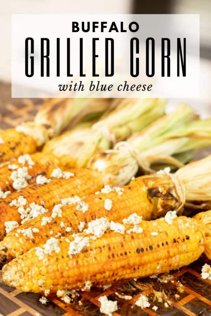 corn on the cobb topped with blue cheese on a wooden cutting board.