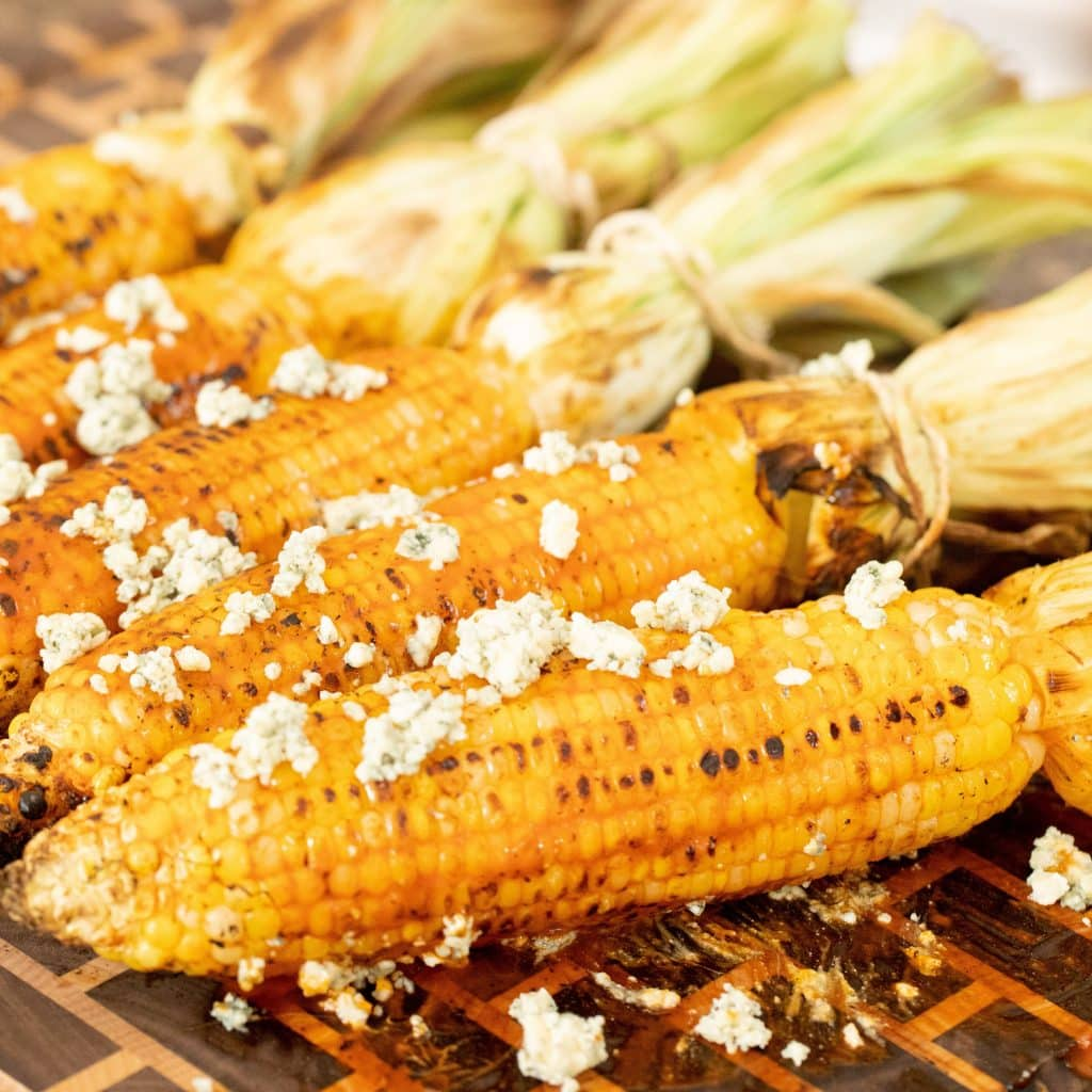 Grilled Corn on the cob top with crumbled white cheese.
