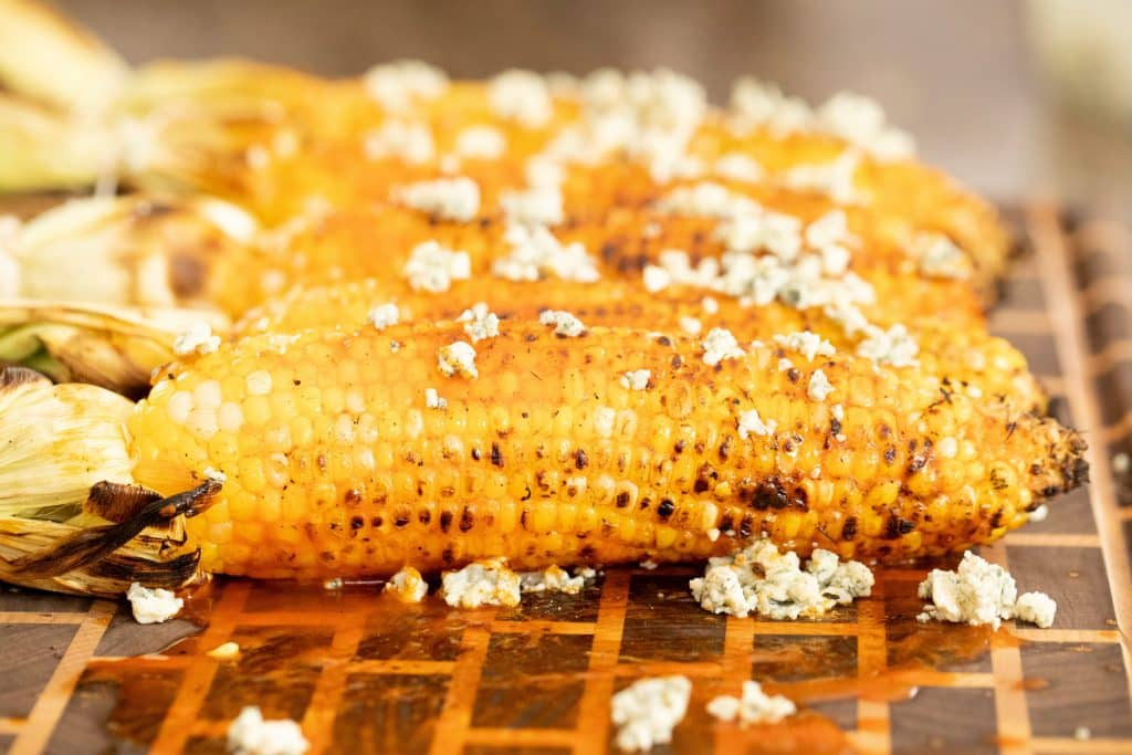 side shot of grilled corn with Buffalo sauce and crumbled blue cheese