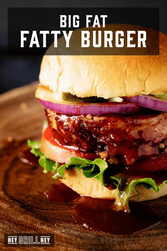 Fatty burger topped with lettuce, onion, and tomato with text overlay - Big Fat Fatty Burger.
