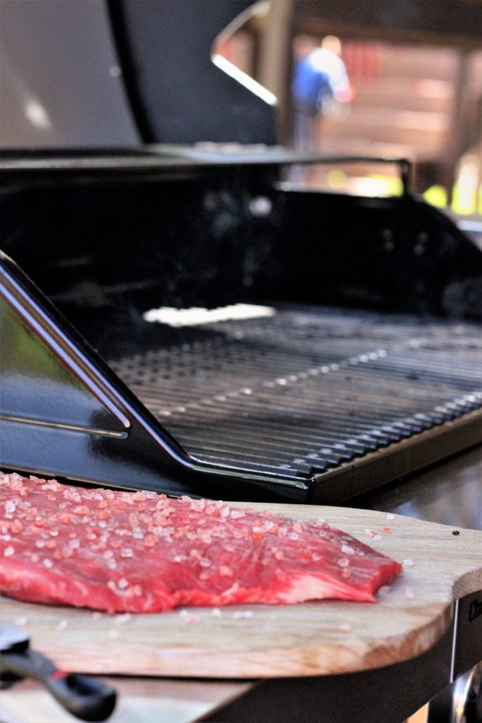 himalayan salted flank steak on a wooden cutting board next to a gas grill