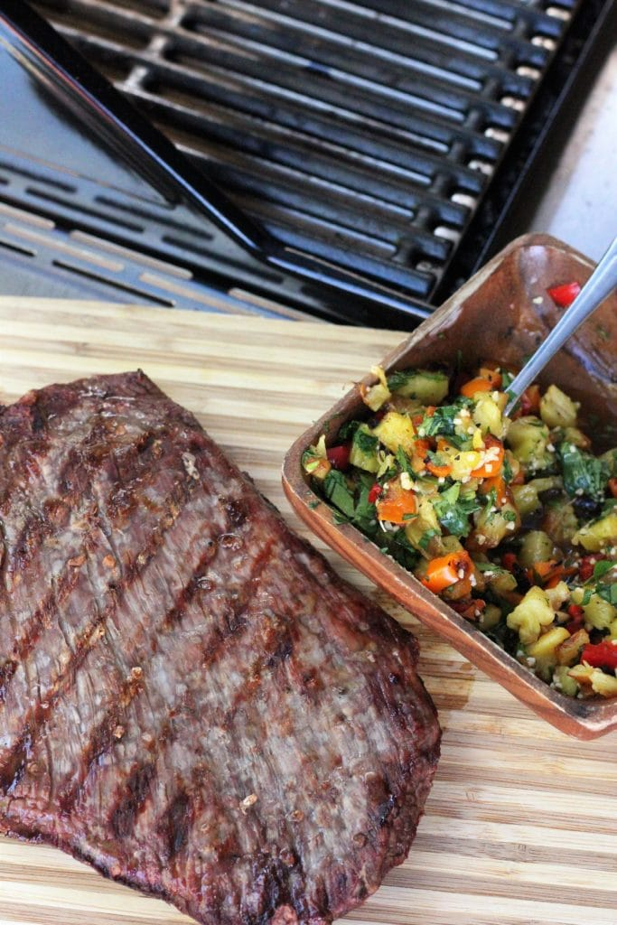 grilled salted flank steak on a wooden cutting board next to a bowl of grilled pineapple salsa