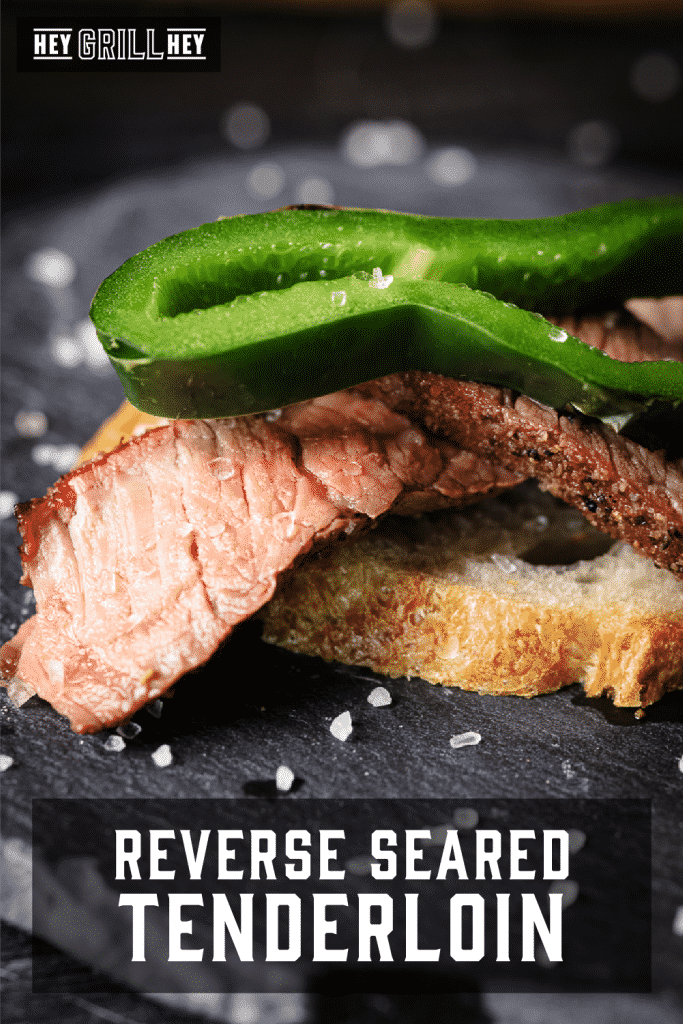 Sliced reversed seared tenderloin topped with a slice of anaheim chile on a roasted crostini with text overlay - Reverse Seared Tenderloin.