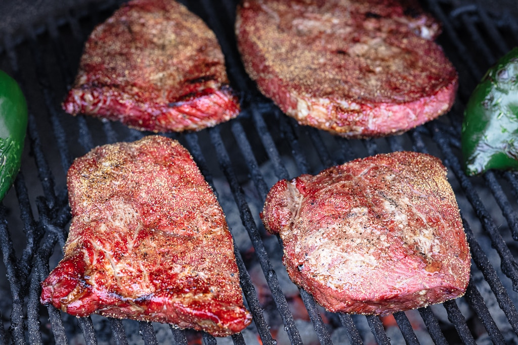 Seasoned steaks on the grill grates of a smoker.