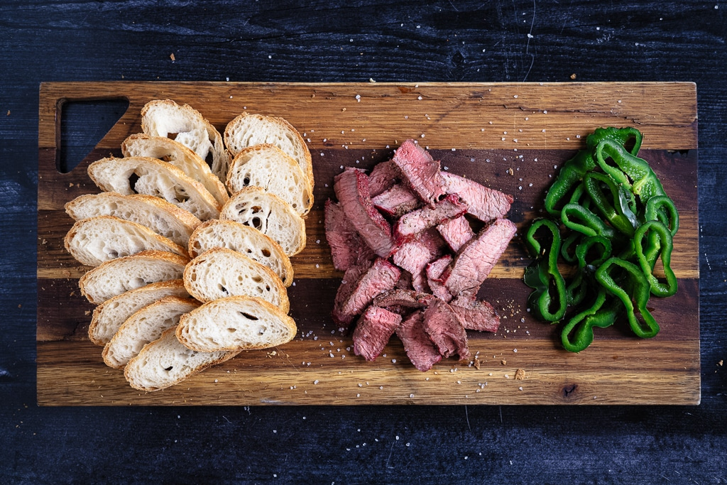 Crostinis, sliced steak, and sliced peppers on a cutting board.