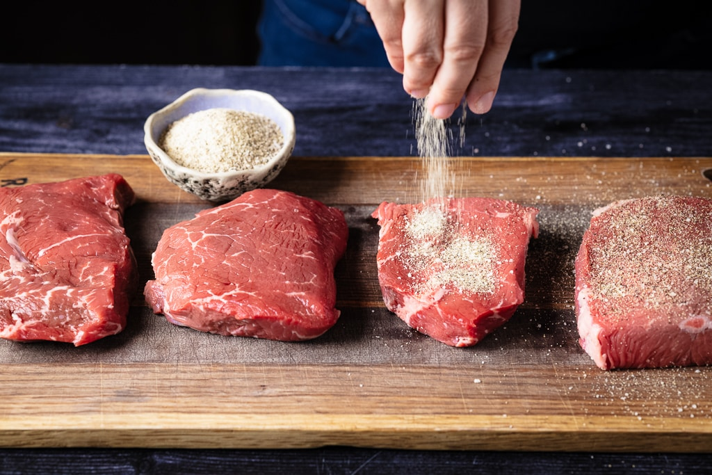 Steaks on a cutting board being seasoned with Beef Rub.