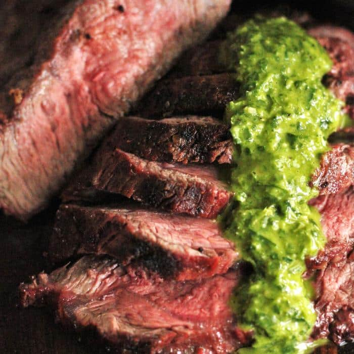 sliced grilled flat iron steak with chimichurri drizzled on the top