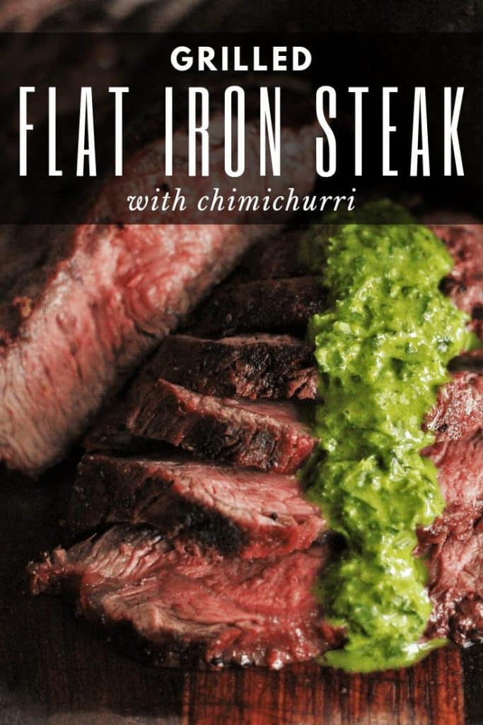 Slices of medium rare flat iron steak shingled on a wood serving board. Topped with a line of green chimichurri sauce.