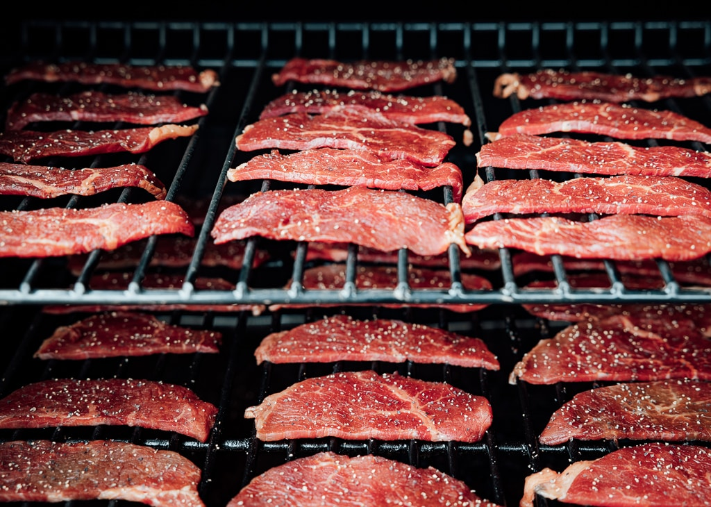 Slices of java beef jerky on the grill grates of a smoker.
