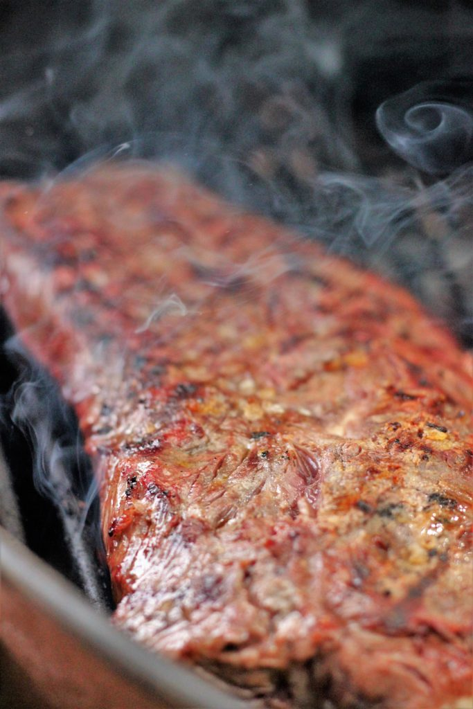 Slightly charred flat iron steak on grill grates with smoke swirling.