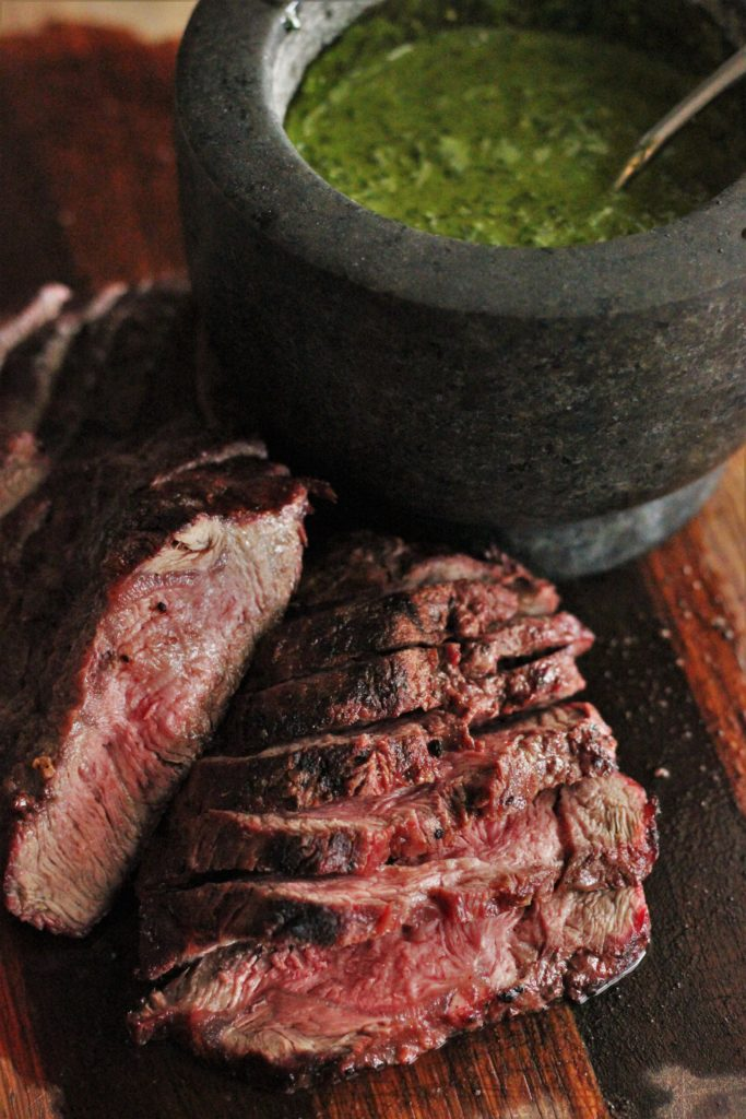 Grilled medium rare flat iron steak sliced and shingled on a wood cutting board in the foreground. Granite bowl of chimichurri in the background.