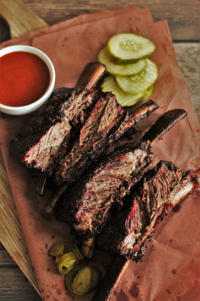 Smoked beef ribs, sliced and served on butcher paper.