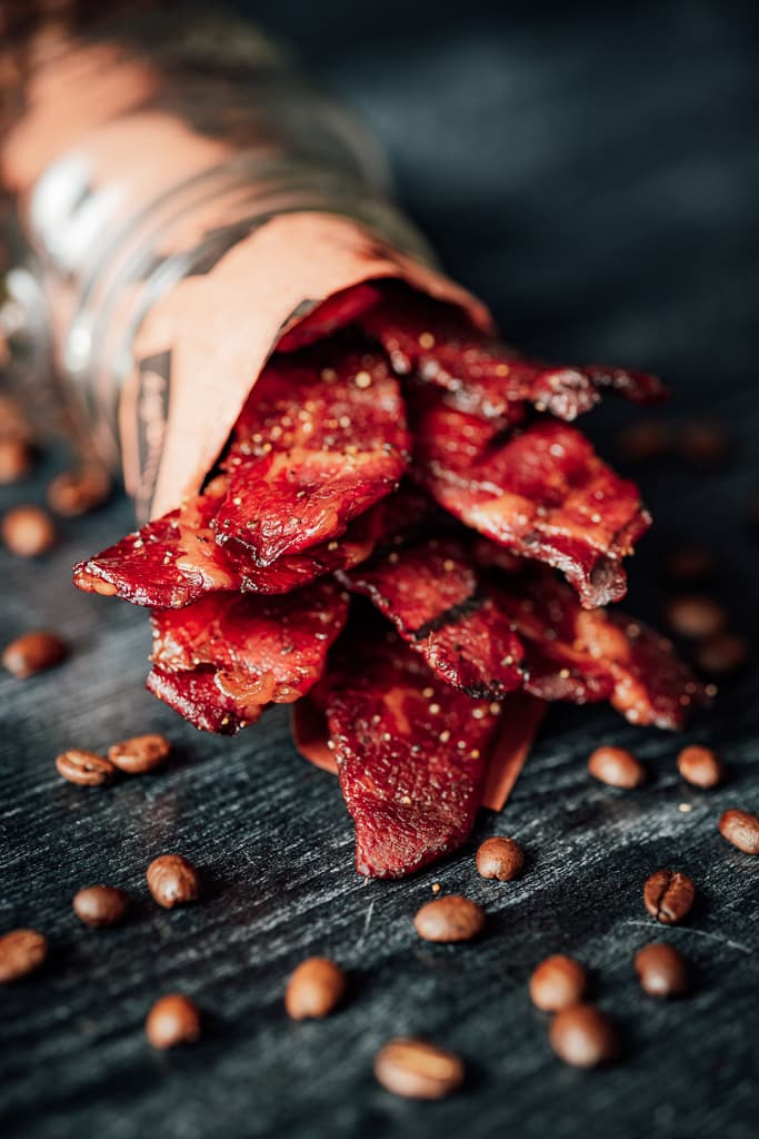 Sweet java beef jerky wrapped in Hey Grill Hey butcher paper surrounded by coffee beans.
