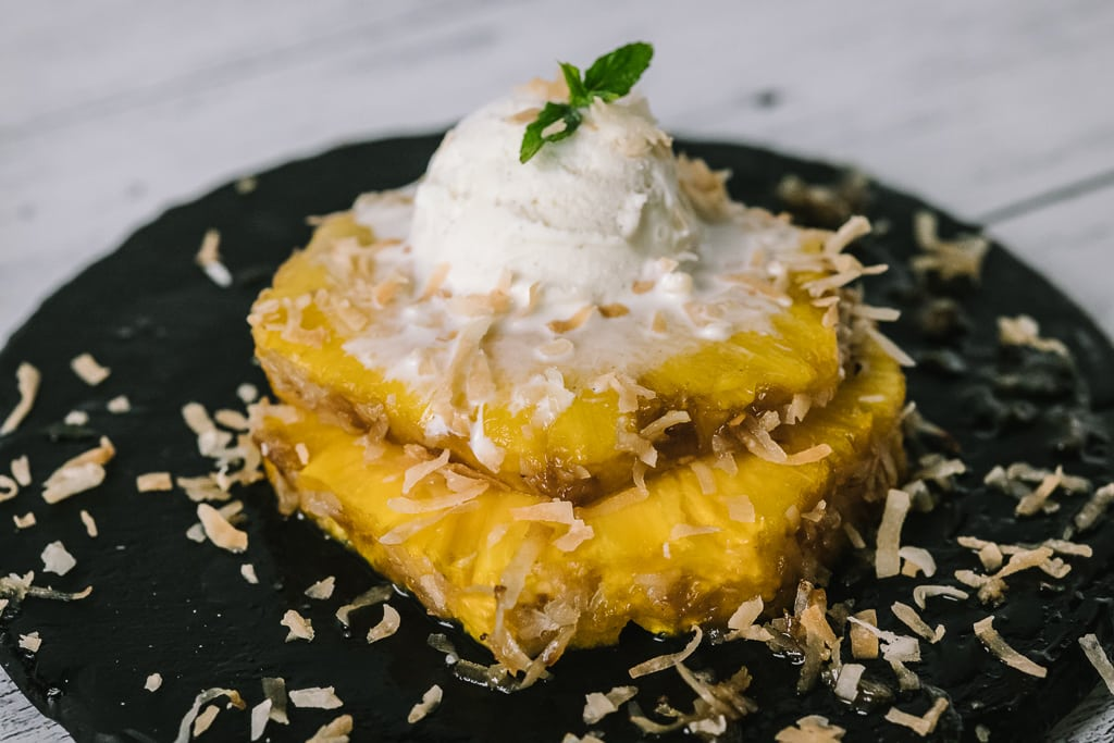 Two rings of pina colada grilled pineapple topped with a scoop of ice cream.