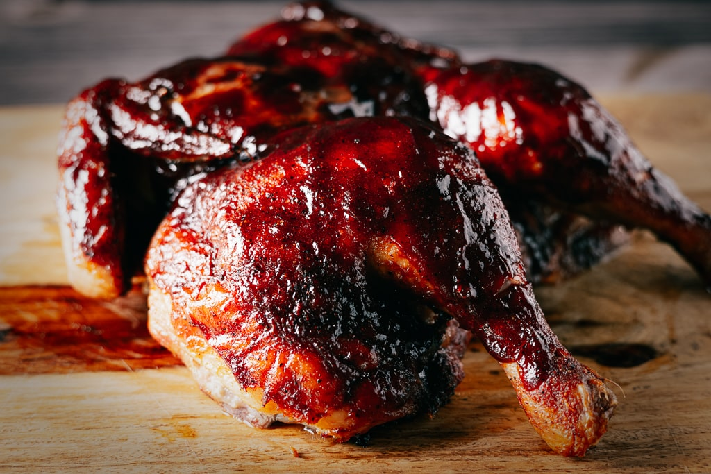 Spatchcock smoked chicken covered with cherry chipotle BBQ sauce on a wooden cutting board.