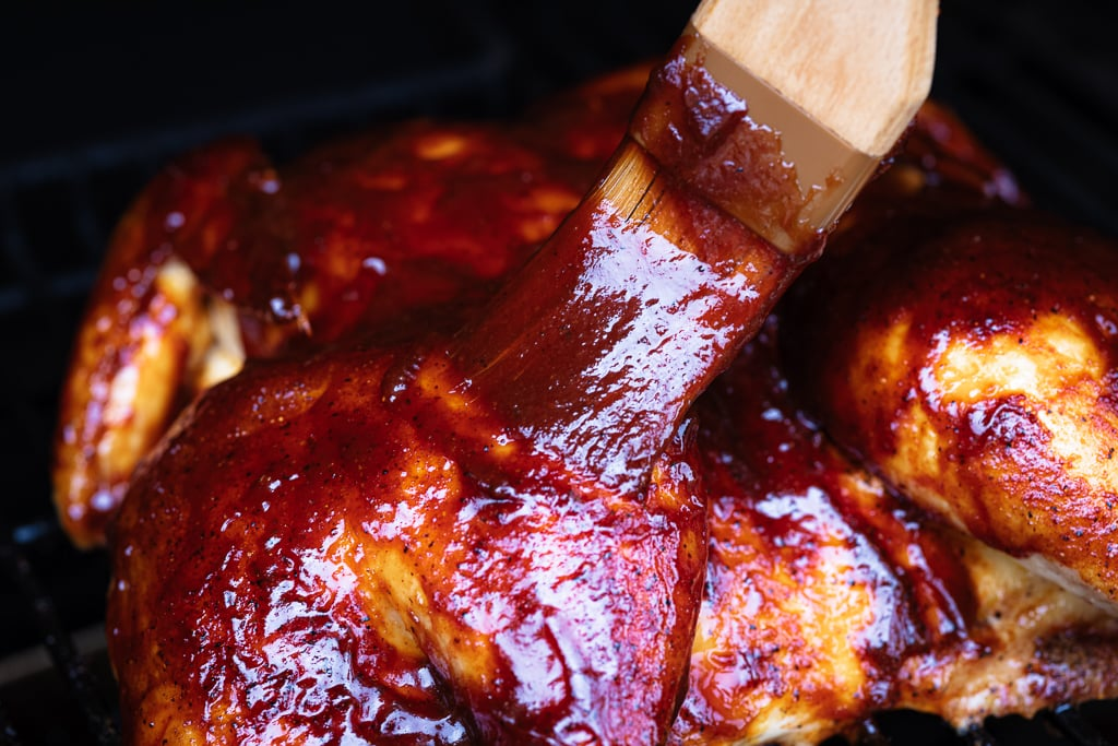 Basting brush spreading cherry chipotle BBQ sauce on a smoked spatchcock chicken.