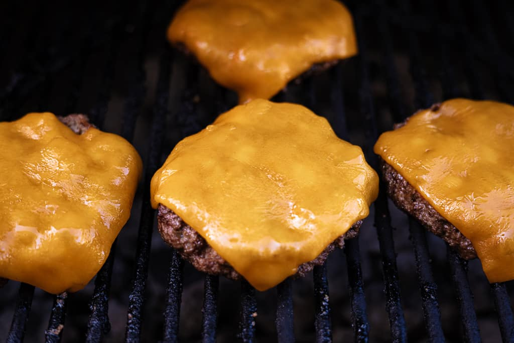 Butter burger patties topped with cheddar cheese on the grill.