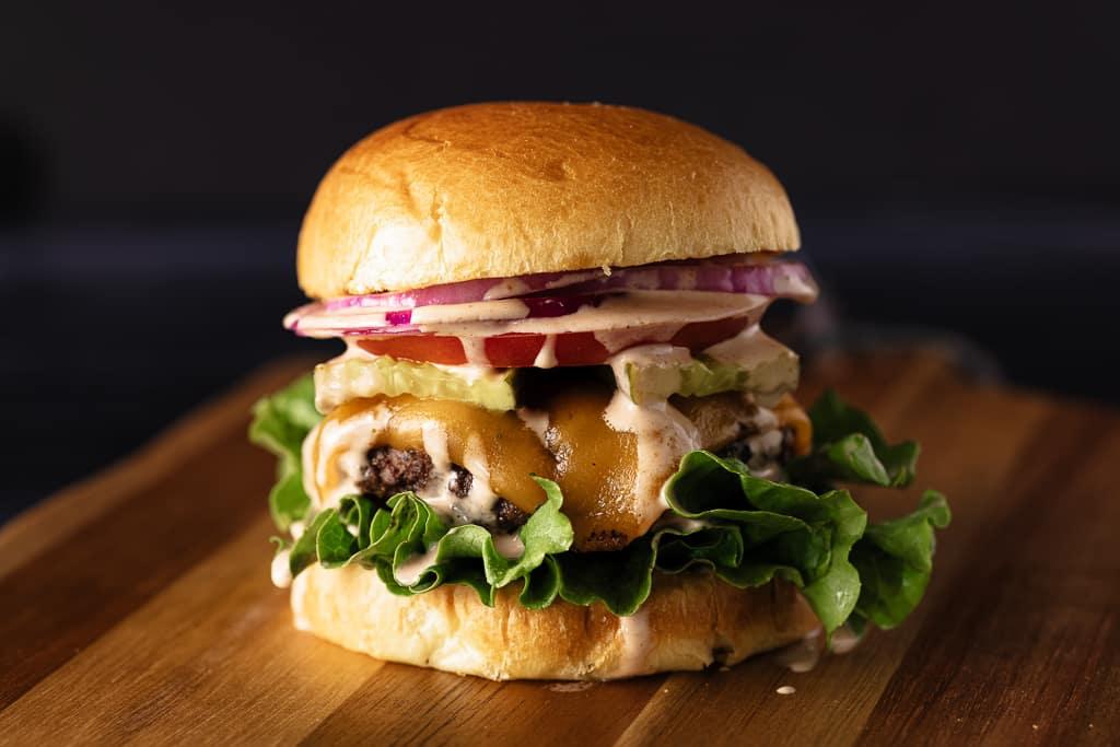 Steakhouse butter burger on a wooden cutting board.