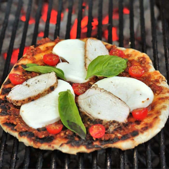 wood fired pizza with red pesto and grilled chicken on a grill over hot coals