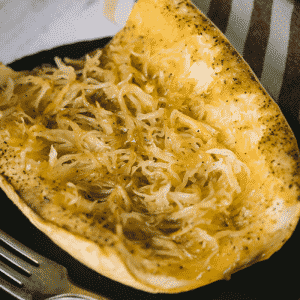 Grilled spaghetti squash on a serving dish next to a metal fork.