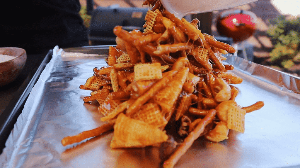 Stack of smoked snack mix on aluminum foil.
