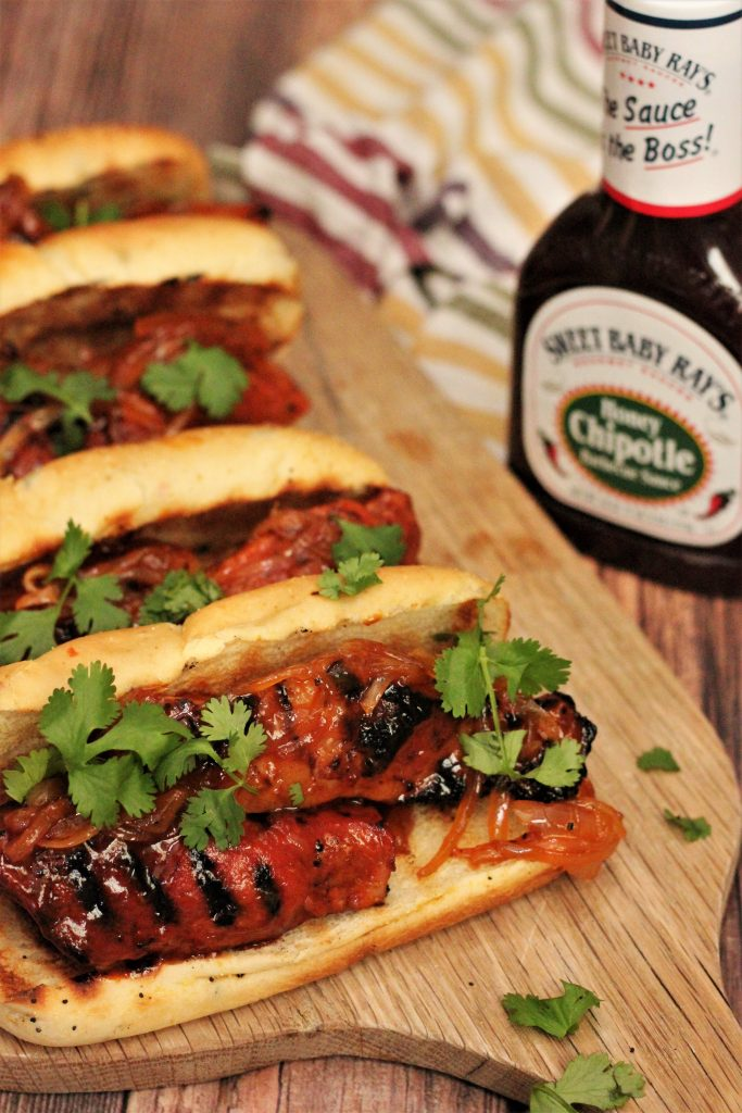 Honey Chipotle Country Style Rib Sandwich topped with cilantro on a wood cutting board with a bottle of barbecue sauce in the background.