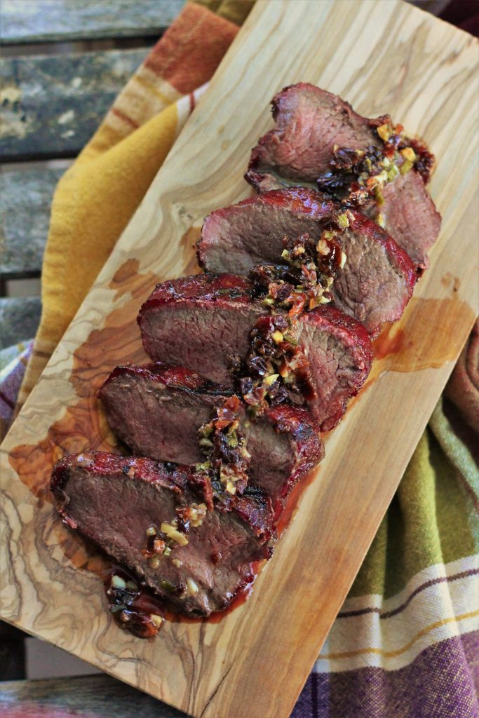 Sliced venison on a wood cutting board drizzled with garnish.