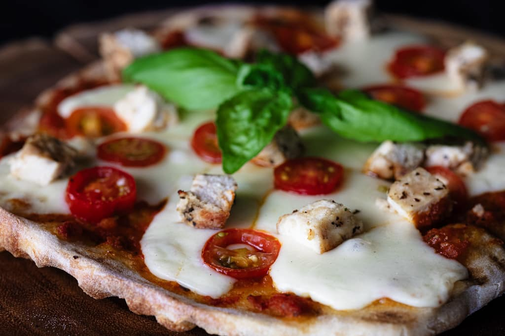 Wood fired pizza topped with fresh mozzarella, grilled chicken, and fresh basil.