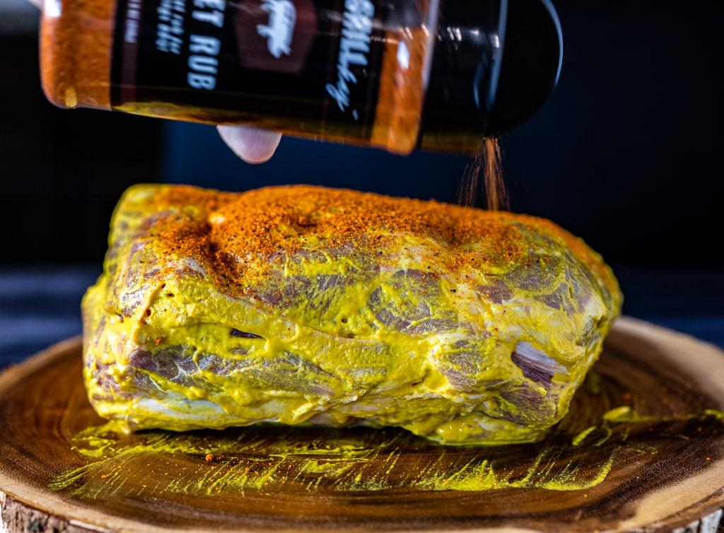Mustard-slathered pork but being seasoned with Hey Grill Hey Sweet Rub.