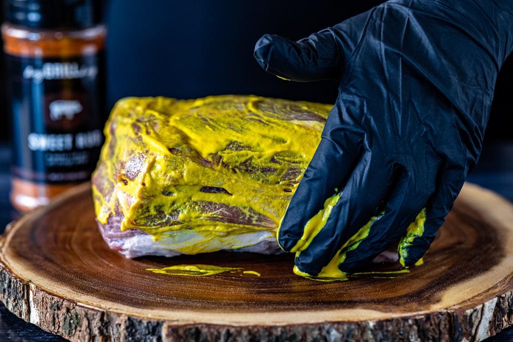 Gloved hands slathering yellow mustard on a pork butt.