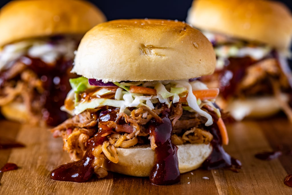 Three smoked pulled pork sandwich on a wooden cutting board.