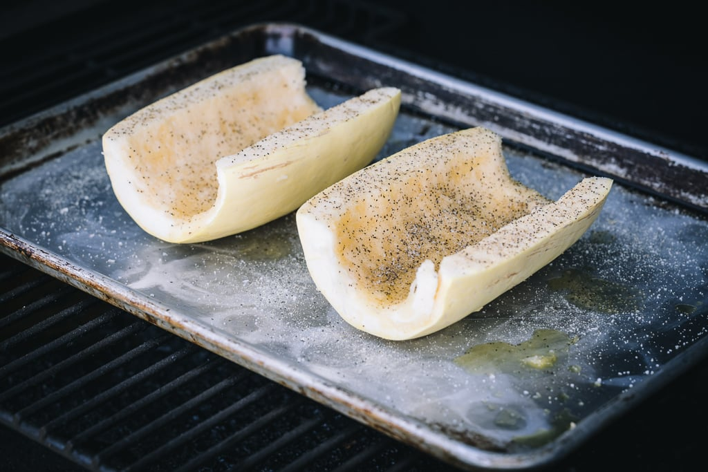 Two seasoned spaghetti squash halves on a baking dish in a grill.